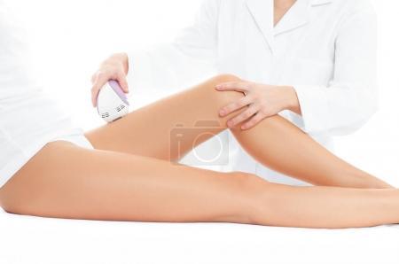 Photo pour Beautician removing hair of woman's leg. Laser depilation treatment in beauty spa. - image libre de droit