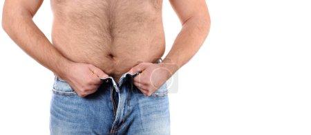 Photo pour Homme en surpoids essayant de fermer les boutons de son jean - image libre de droit