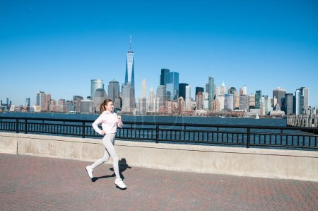 Photo for Healthy lifestyle. Woman is running in New York City. Fitness sports runner is jogging in Liberty State Park - Royalty Free Image