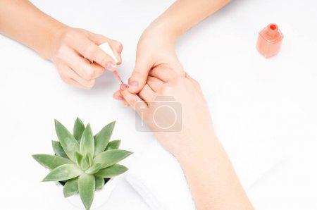 Photo pour Manucure s'applique le vernis à ongles sur le doigt. Manucure. Concept de soins et de spa des mains - image libre de droit