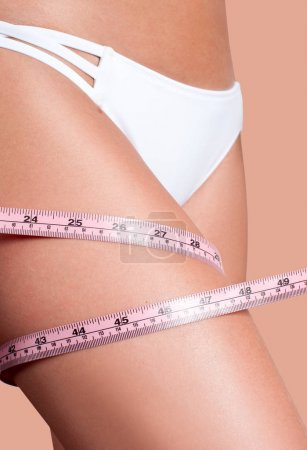 Photo for Successful weight loss. Woman measuring her leg with a measure tape - Royalty Free Image