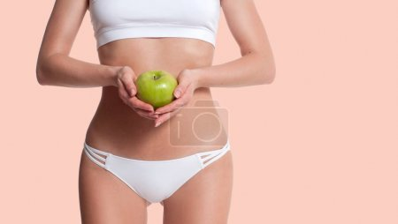 Photo for Beautiful slim woman with perfect sporty body holding apple. Diet concept and successful weight loss. Pastel background - Royalty Free Image