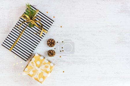 Top view of gift boxes wrapped in black and white striped and golden dotted paper with pine and cones on a white wood background. Christmas presents preparation.