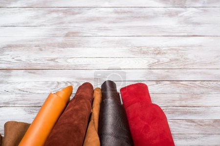 Brightly colored leather in rolls on white wooden background. Leather craft. Copy space.