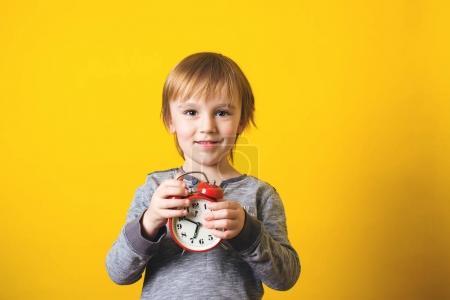 Photo pour Mignon petit garçon avec réveil sur le fond jaune. - image libre de droit
