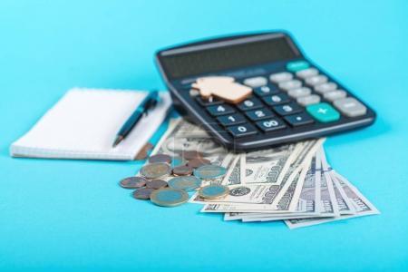 Photo pour Le concept d'épargne financière pour acheter une maison. Maison modèle, dollars, pièces et calculatrice isolés sur le fond bleu . - image libre de droit
