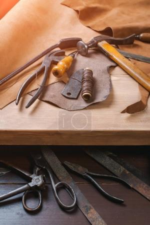 Photo pour Outils Cobbler en atelier sur une table en bois. Vue du dessus . - image libre de droit