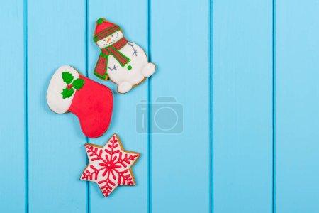 Photo pour Biscuits colorés de pain d'épice de Noël sur le fond bleu en bois. Concept vacances d'hiver. Espace pour le texte . - image libre de droit