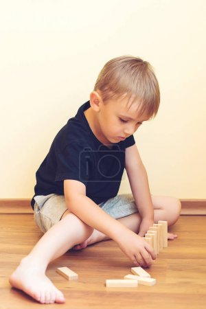 Photo for Cute boy playing on the floor with wooden blocks. Developing toys. - Royalty Free Image