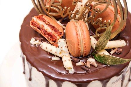 Photo pour Gâteau d'anniversaire décoré de macarons dorés, vue sur le haut. Élégant gâteau nu surmonté de chocolat. Concept de fête d'anniversaire - image libre de droit