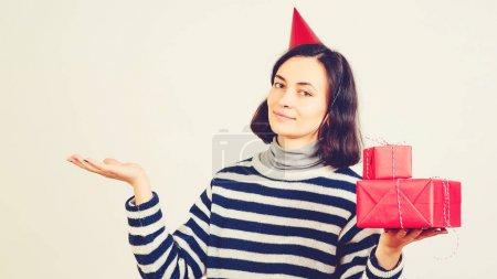glückliche Frau hält Weihnachtsgeschenke über Weiß. Weibchen mit leerer Handfläche für die Werbung für Ihr Produkt.