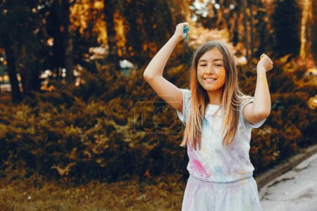 Photo for Beautiful girl with a colorful dry paints. Little lady have fun in a summer park - Royalty Free Image