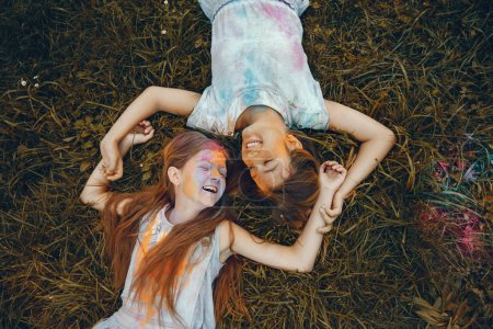 Photo for Beautiful girls with a colorful dry paints. Friends have fun in a summer park - Royalty Free Image