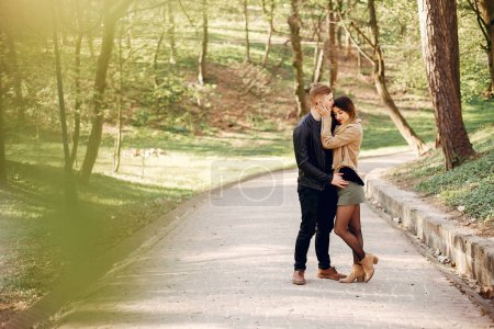 Photo for Cute couple in a park. Lady in a brown jacket. - Royalty Free Image