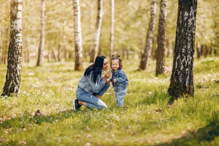 Photo for Beautiful mother with daughter. Family in a spring park. Woman in a blue jacket - Royalty Free Image