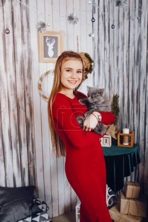 Photo for Cute little girl playing with gray cat. Lady in a studio - Royalty Free Image