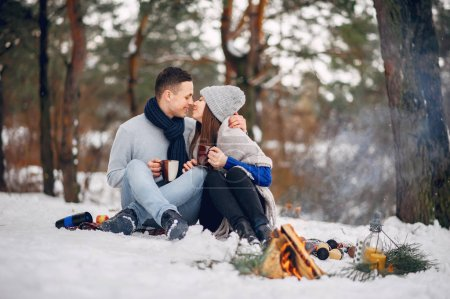 Photo for Couple in a winter forest. Beautiful girl in a blue sweater. Boy and girl drinking a tea - Royalty Free Image
