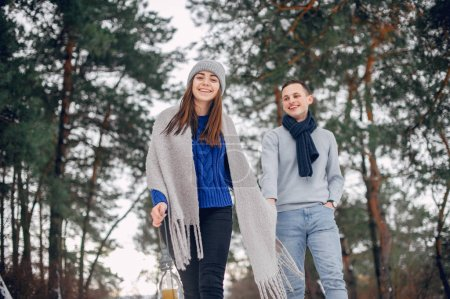 Photo for Couple in a winter forest. Beautiful girl in a blue sweater. Boy and girl with candle - Royalty Free Image