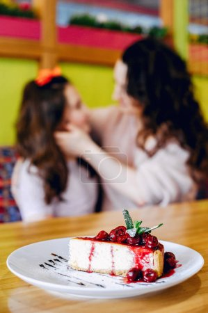 Photo pour Beautiful mother with daughter. Family in a cafe. Girl with a dessert - image libre de droit