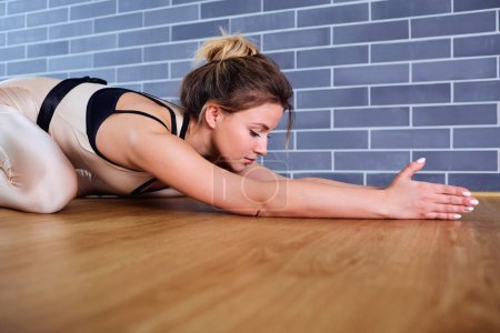 Girl in white clothes in yoga position on the floo