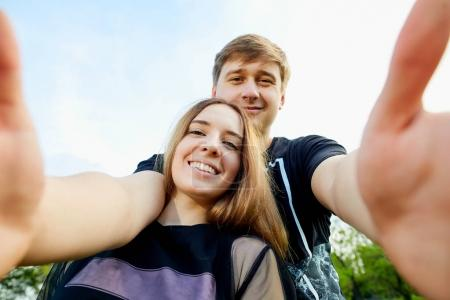 Photo for Couple makes selfie on the phone outdoors. - Royalty Free Image
