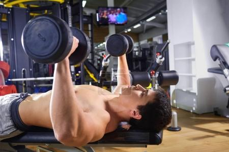 A guy with dumbbells lying doing exercises in the gym