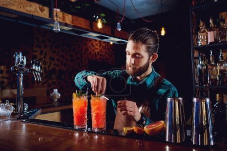 Bartender with a beard makes a cocktail behind counter in the ba