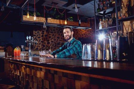 Photo pour Un barman barbu derrière le comptoir dans le bar . - image libre de droit