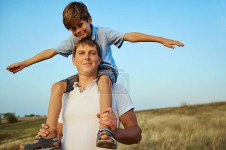 Photo pour Fils sur les épaules de son père à l'air libre dans les champs. Fête des Pères . - image libre de droit