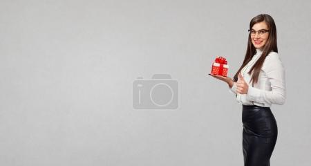 Photo for The brunette girl in a shirt and skirt with a gift in hands on a gray background. - Royalty Free Image
