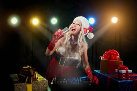 DJ girl in santa hat sings into microphone on Christmas day.