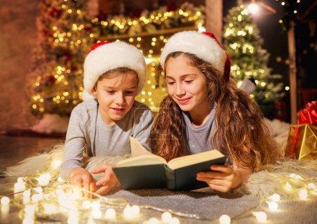 Photo pour Deux enfants par terre lisent un livre dans une pièce décorée de décorations de Noël . - image libre de droit