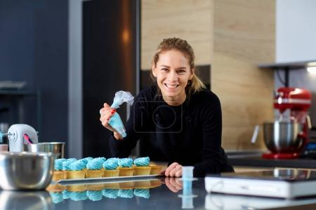 Photo for The confectioner with a pipping bag of cream in his hands decoretion cupcake on the table in the kitchen of a pastry shop. - Royalty Free Image
