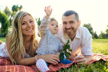Photo pour Bonne famille dans un parc en été automne. Mère, père et bébé jouent dans la nature aux rayons du coucher du soleil . - image libre de droit