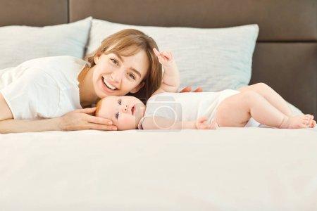 Foto de Mamá y el bebé están mirando la cámara acostado en la cama. Día de las madres. - Imagen libre de derechos