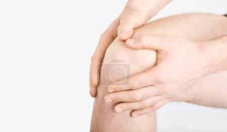 Photo pour Traumatisme, douleur, genoux. Rupture ligamentaire. Rupture du ménisque. Un homme en sous-vêtements tient son genou avec une main sur un fond gris . - image libre de droit