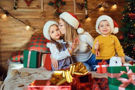 Photo pour Mère et enfants avec des cadeaux dans la maison pour Noël. - image libre de droit