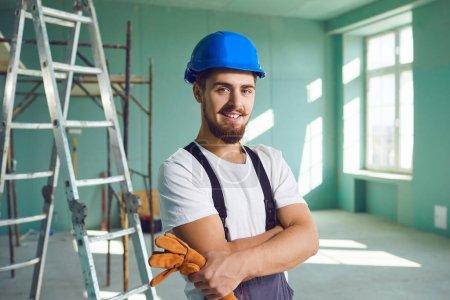 Photo pour Entrepreneur constructeur barbu homme en casque souriant tout en se tenant à l'intérieur sur un chantier de construction.Ouvrier de la construction sur le chantier de construction . - image libre de droit