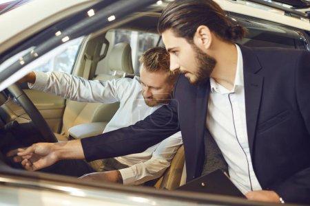 Photo pour Le revendeur automatique montre une nouvelle voiture à un homme dans une salle d'exposition de voiture. - image libre de droit