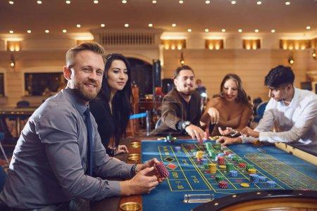 Foto de Una mujer feliz sonriendo toma una victoria en el casino de la ruleta de póquer.. - Imagen libre de derechos