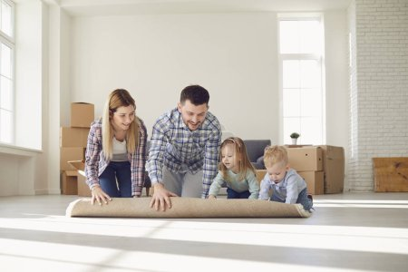 Photo for Happy family with carpet on the floor in a new apartment. Moving move Relocation concept new house home apartment rental housing. - Royalty Free Image