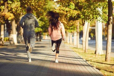 Photo pour Un homme et une femme en tenue de sport courent le long de la rue de la ville le matin. Les coureurs courent dans la ville.. Jogging. La santé. Mode de vie sain . - image libre de droit
