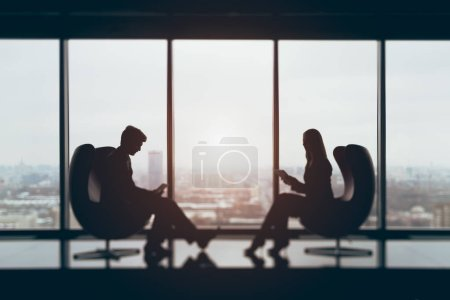 True tilt shift shooting of businessman and businesswoman sitting in front of each other with their gadgets in contemporary office interior, blurred view from top of winter city in background