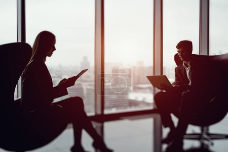 True tilt shift shooting of businessman with a laptop and businesswoman sitting in front of each other next to big office window with their gadgets in contemporary office interior, blurred view from top of city in background