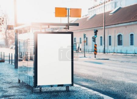 Photo for Glass city bus stop with mock-up of information poster, vertical blank billboard near road, empty white placeholder frame in urban settings with copy space for logo or advertising text on sunny day - Royalty Free Image