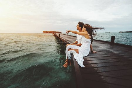Woman in white long dress is showing to her friend something on horizon during beautiful sunset on Maldives island while they both sitting on wooden bridge and smiling, ocean villas in background