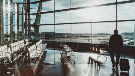 Photo pour Hall contemporain de la gare de dépôt ou terminal de l'aéroport dans la zone de départ avec silhouette de touriste adulte avec son sac sur roues en face de la façade vitrée à côté de rangées vides de sièges en bois - image libre de droit