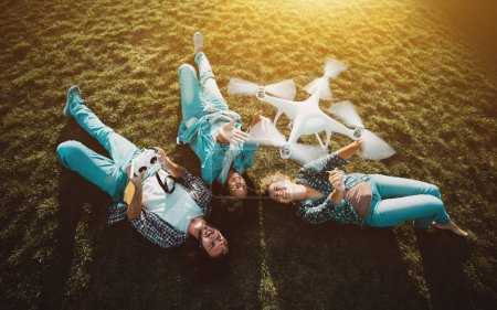 Photo for Group of three happy people: two girls of different races and one guy are laying on the meadow and posing to the drone, which is flying over them, operated by the bearded guy and capturing video - Royalty Free Image
