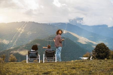 Group of three friends observing landscape from the mountain