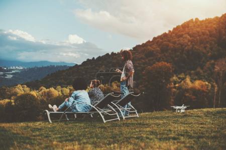 Friends in autumn glade enjoying scenery